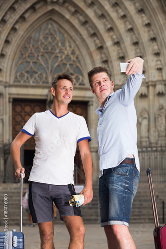Sticker  Male couple with luggage doing selfie picture at travel