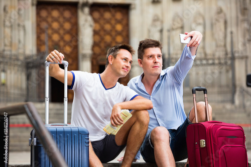 Wall mural Two guys with luggage  taking selfie in city at summer day