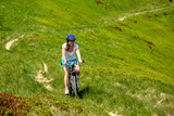 Woman rides bicycle up in the mountains