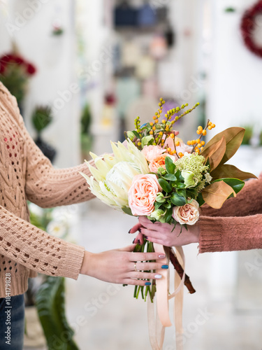 Plexiglas Hydrangea Woman buying a bouquet of peonies and hydrangeas at a flower shop. Small floral business owner. Female power startup concept