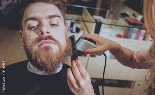 Plexiglas Kapsalon Master cuts hair and beard of men, hairdresser makes hairstyle for a young man. Hipsters