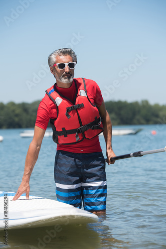 man next to a stand-up paddle board on the lake
