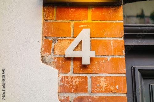 steel number 4 door sign on brick facade - 184189093