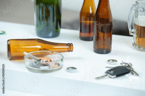 Beer bottles, ashtray and keys on white surface