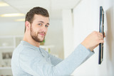 man putting picture frame onto wall - 184189891