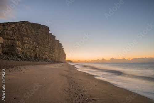 Staande foto Cappuccino Beautiful vibrant long exposure sunrise landscape image of West Bay in Dorset England