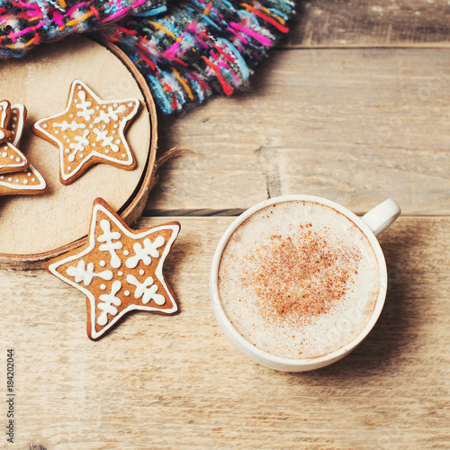 Sticker Gingerbread with cup of coffee and cozy scarf on wooden background