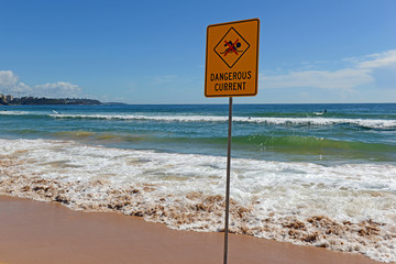 Dangerous Current sign, warning swimmers and surfers of the rough water where they are recreating off the beach