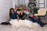 smiling girl and boy playing on the floor with his dog on the background of the New Year tree. Christmas and New Year. Samoyed and his family in a cozy room. family on Christmas