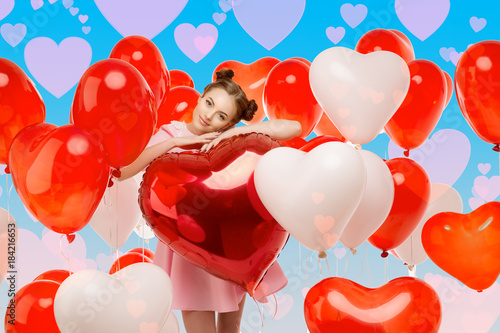 Beautiful girl with balloons in the shape of hearts, flies into the sky. Fantasy on the theme of Valentine's Day. Woman model in vanilla pink dress in love.