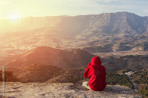 Foto op Canvas Beige Sitting at the highest peak of the mountain watching the beautiful sunset landscape, wearing a red coat