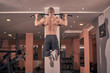 one young bodybuilder, rear view, exercise pull-up bar, gym indoors. full lenght shoot.
