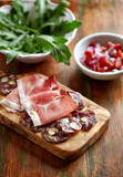 Mediterranean-style Antipasto; cured ham, sausage with nuts on chopping board - 184219617