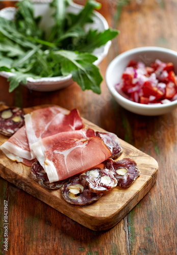 Mediterranean-style Antipasto; cured ham, sausage with nuts on chopping board