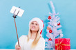 Woman in Santa hat taking Christmas selfie