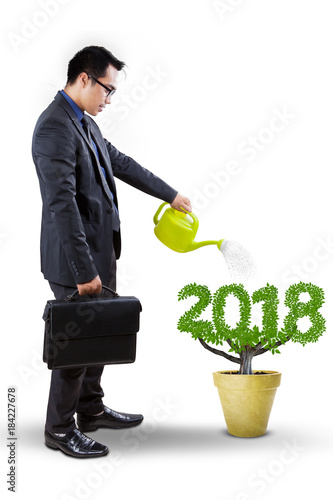 Male manager watering a plant on studio