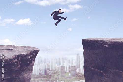 American businessman jumping through gap cliff