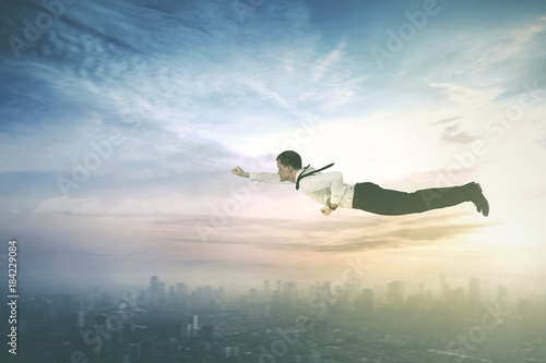 American businessman flying with a superhero pose