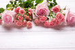 Border from tender pink roses flowers  on  white wooden background.