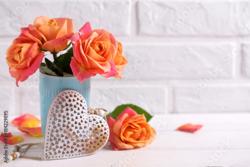 Fresh orange roses in blue cup and decorative heart
