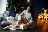 Beautiful smiling girl in a white pullover near chrismas tree - 184243282