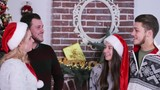Close-up portraits of two cute couple talking and smiling each other on Christmas tree and fireplace backround. - 184243426