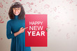 Happy asian woman showing red board with Happy New Year text
