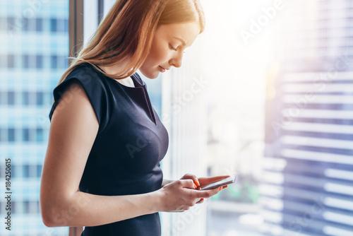 Fototapeta Pretty smilingwoman using smartphone standing in office