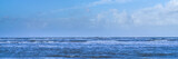 Wind turbines in the North Sea, view from the beach, panorama