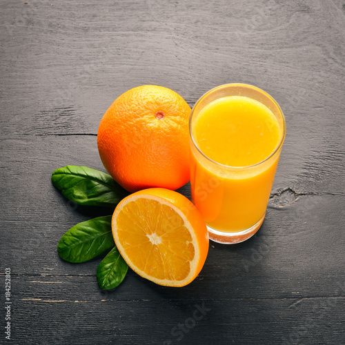 Foto op Canvas Sap Orange fresh juice and oranges on a wooden surface. Top view. Free space for text.