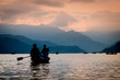 Silhouettes of people on boats at sunset on Phewa lake. Vanilla sky and mountain background. - 184254429