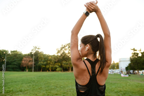 Back view portrait of a fitness woman in earphones stretching