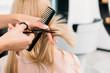Leinwandbild Motiv cropped image of hairdresser trimming ends of blonde hair