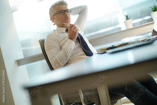 Wall mural Businessman talking on phone in office, relaxing in chair
