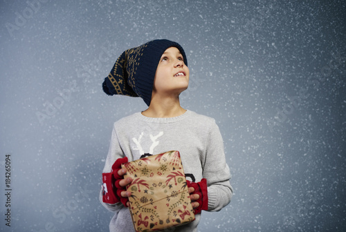 Foto Murales Boy with gift box looking at snow .