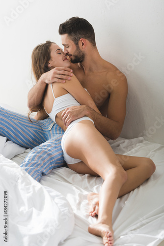 happy young couple embracing and kissing in bed in morning buy