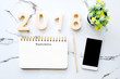 2018 resolution on blank notebook paper and smart phone on white marble background, new year business and technology concept, template