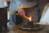 Man lighting candle in church - 184279448