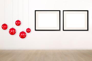 Parete bianca con palle rosse di Natale e due cornici vuote