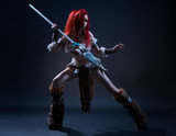 Beautiful red haired woman in stone age clothing with spear posing at camera on dark background - 184292446