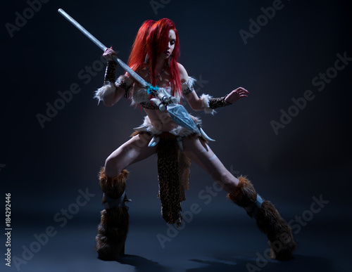 Beautiful red haired woman in stone age clothing with spear posing at camera on Poster