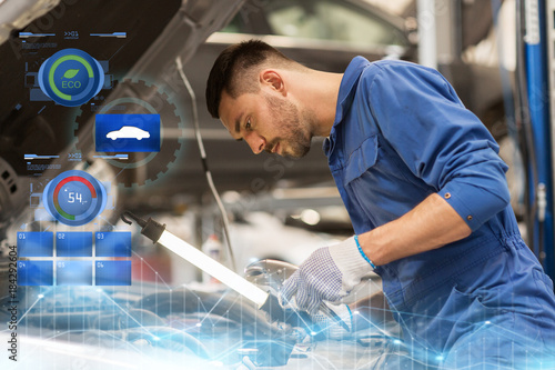 mechanic man with lamp repairing car at workshop - 184292604