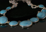 Turquoise necklace with silver chain on black background