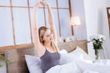 Laid-back morning. Charming young woman sitting in her bed and stretching herself while smiling brightly