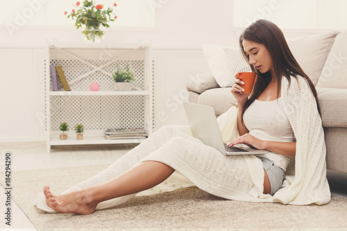 Cozy home. Girl in a plaid with a laptop and a cup Poster