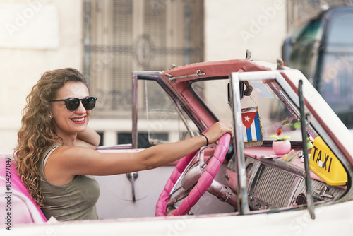 In de dag Havana Beautiful woman tourist driving a classic car in Cuba.