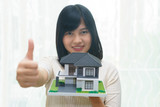 Happy young woman thumps up or like with house model on hands. - 184298822