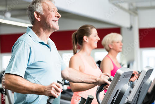 Poster Happy seniors train on cross trainer with personal trainer at the gym