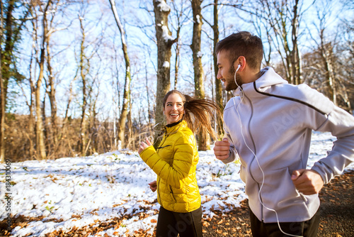 Handsome lovely young healthy couple running with earphones and sportswear through the forest in the winter morning.