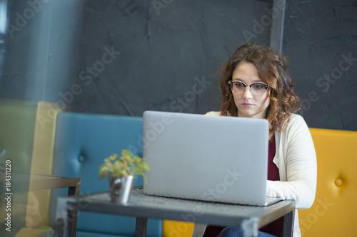 studentessa con gli occhiali è immersa davanti al suo computer in un locale con divani coloratie